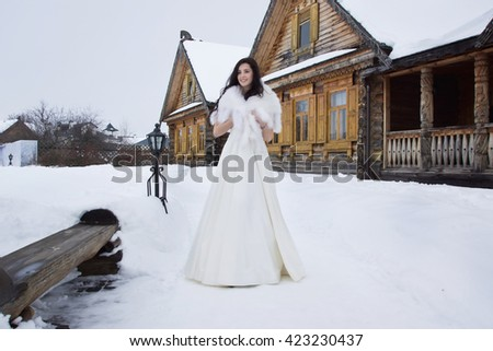Russian wedding. The bride in a fur cape in winter snowy village