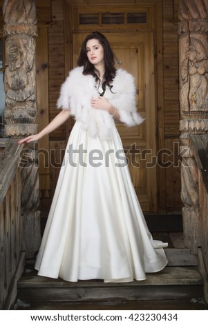 Russian wedding. The bride in a fur cape on porch of wooden house