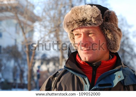 Russian winter. A smiling man in a fur hat - stock photo