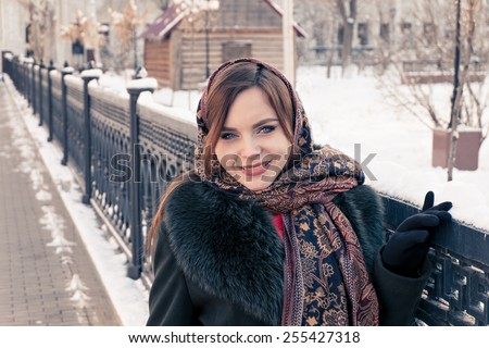 Russian woman in winter weared in traditional shawl near fence, toned image - stock photo