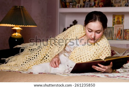 Russian woman reading with her cat in bed room