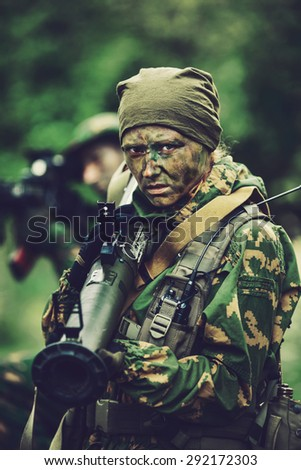 Russian woman soldier with a grenade launcher in his hands in forest area at twilight