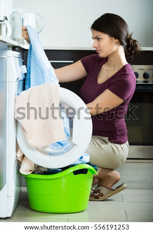 russian woman with musty towels after laundry at home