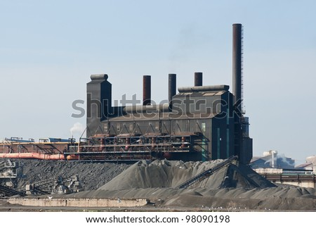 Rust Belt Steel Mill:   A large steel manufacturing plant surrounded by piles of coal and coke located in the American rust belt city of Cleveland, Ohio