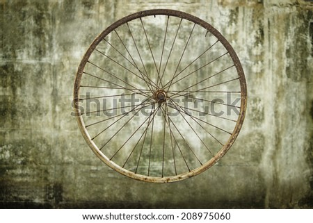 Rust bicycle wheel on wall background - stock photo
