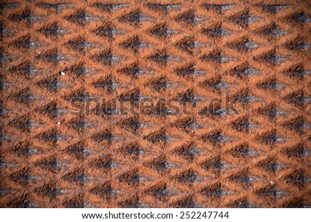 Rust colored piece of iron an a city man-hole cover.  Iron.  - stock photo