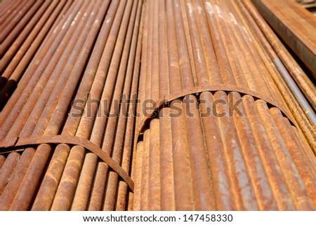 Rust steel bar bunch in warehouse - stock photo