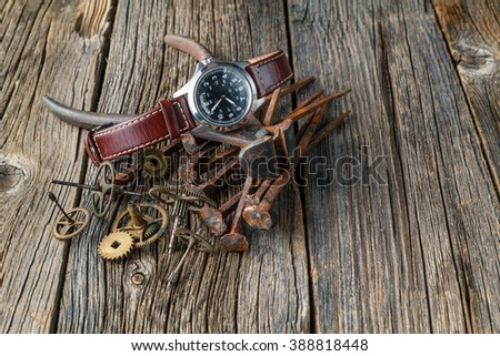 rust watch gear on dark wooden table - stock photo