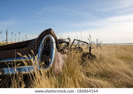 Rusted abandoned car in a field - stock photo