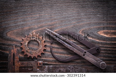 Rusted antique measuring calipers with gear wheel on vintage dark wooden background top view construction concept. - stock photo