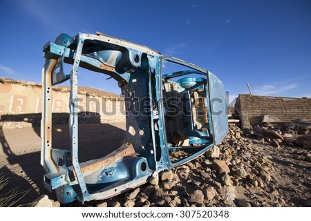 Rusted blue old car frame left in a remote village early in the morning against a blue sky. Bolivia - stock photo