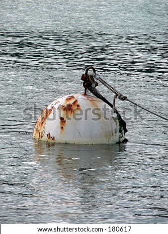 Rusted buoy in water - stock photo