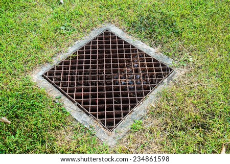 Rusted iron drain and green grass in the garden   - stock photo