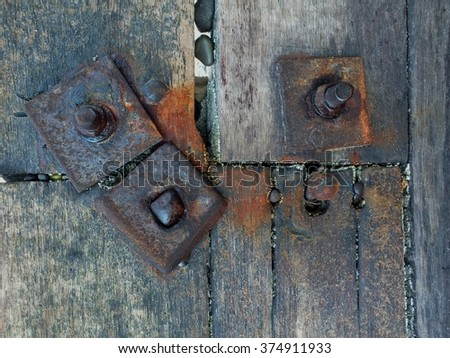 rusted metal bolts close up on wooden beach breakers, interesting textures and colours, abstract image , age, decay