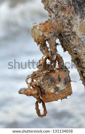 Rusted padlock against blurred water surface - outdated security and anti virus software metaphor - stock photo