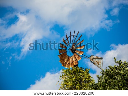 Rusted windmill framed by clouds and trees against blue sky. - stock photo