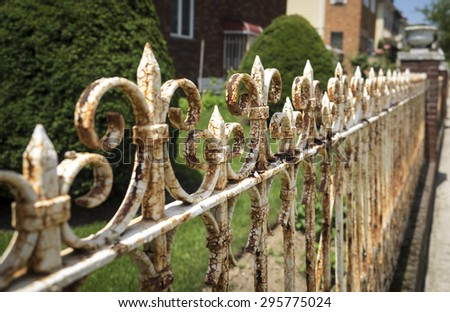 Rusted wrought iron fence with weathered paint - stock photo