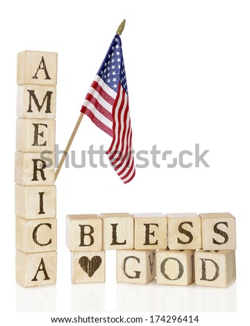 "Rustic alphabet blocks arranged to say ""America, Bless God,"" with an American flag flying above.  On a white background. - stock photo"