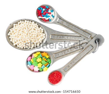 Rustic aluminum measuring spoons with different kinds of cookie sprinkles isolated on white with working path - stock photo