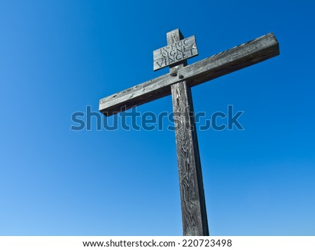 Rustic and Weathered Cross against Blue Sky - stock photo