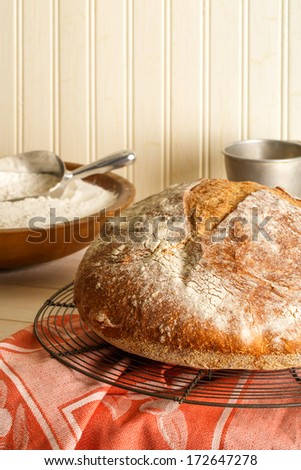 Rustic artisan bread cools on a wire baking rack resting on a sunlit table surrounded by baking utensils and a bowl of flour. - stock photo