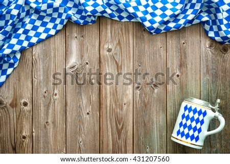 Rustic background for Oktoberfest with Bavarian white and blue fabric and a beer stein