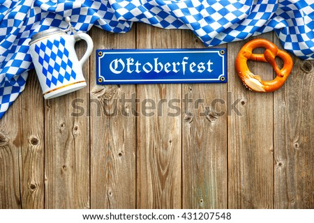 Rustic background for Oktoberfest with Bavarian white and blue fabric, beer stein and soft pretzel - stock photo