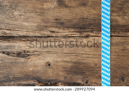 Rustic background for Oktoberfest with bavarian white and blue ribbon - stock photo