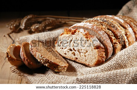 Rustic background of assorted freshly baked sliced rye bread arranged in a single loaf showing the texture for an artistic bakery display - stock photo