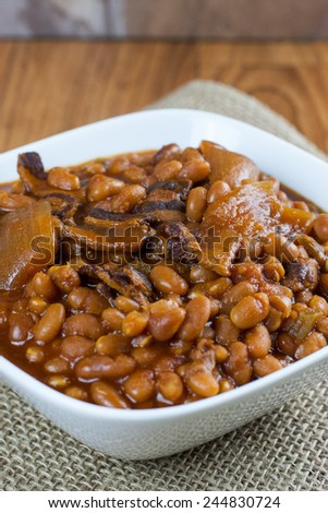 Rustic baked beans in a white bowl on a burlap placemat and wooden table. - stock photo