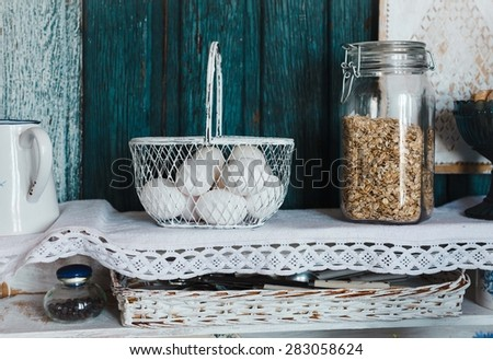 Rustic Basket of eggs and jars of oatmeal over on kitchen shelves.