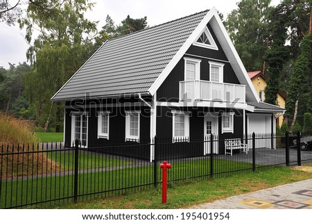 Rustic black and white wooden summer cottage near the forest - stock photo
