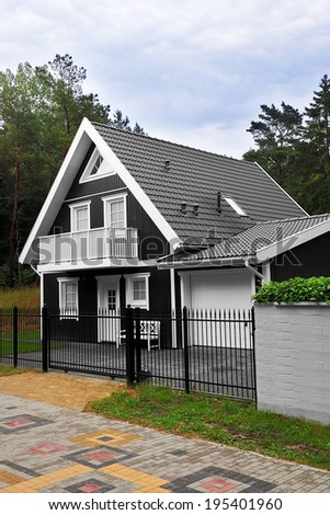 Rustic black and white wooden summer cottage near the forest