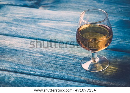 Rustic blue wooden table with cognac glass.