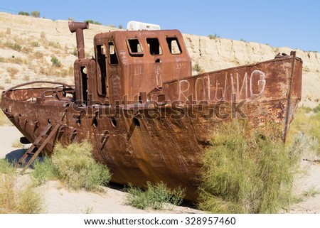 Rustic boats on a ship graveyards on a desert around Moynaq, Muynak or Moynoq - Aral sea or Aral lake - Uzbekistan, Central Asia. - stock photo
