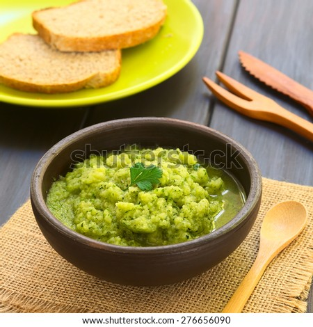 Rustic bowl of homemade zucchini and parsley spread garnished with fresh parsley leaf, slices of wholegrain bread in the back, photographed with natural light (Selective Focus, Focus on the leaf)  - stock photo