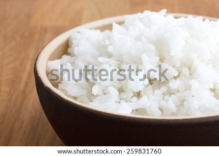 Rustic bowl of white rice on wood surface. Detail. - stock photo
