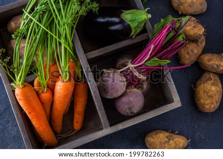 Rustic box with fresh carrots, beetroot, aubergine and new potatoes