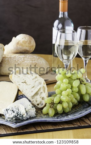Rustic bread and cheese platter with grapes and wine - stock photo