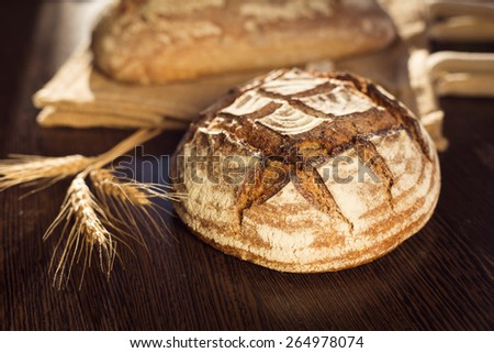 Rustic bread and wheat on a traditional cloth bag - stock photo
