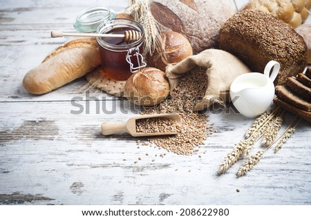 Rustic bread and wheat on an old vintage planked wood table.  - stock photo