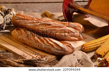 Rustic bread and wheat on an old vintage wood table and chest. - stock photo