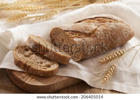 Rustic bread and wheat on wood table - stock photo