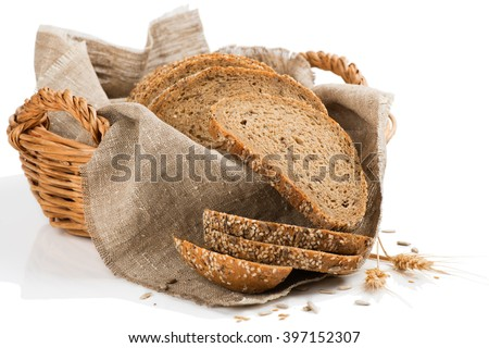 Rustic bread in a basket and wheat isolated on a white background.