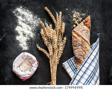 Rustic bread roll or french baguette, wheat and flour on black chalkboard. Rural kitchen or bakery. - stock photo