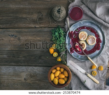 Rustic breakfast set. Russian cheese cakes on vintage metal plate with lingonberry jam, fresh kumquats, thyme, rope and old dinnerware over a rough wood background with a copy space. Top view - stock photo