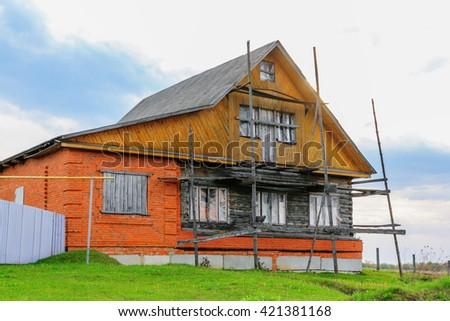 Rustic brick and wooden cabin in a rural country - stock photo