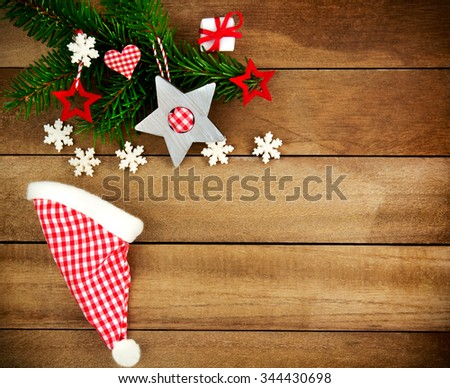 Rustic brown wooden background decorated with green fir branch, red and red and white checkered stars and santa hat, gift and snowflakes as christmas decoration in Country Style