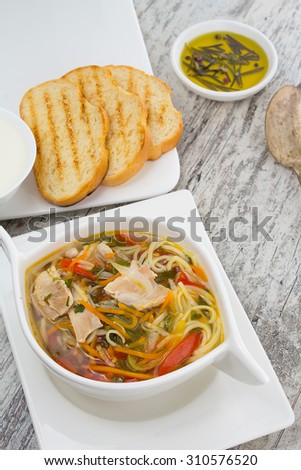 rustic chicken soup with noodles and vegetables close-up over wooden vintage background - stock photo