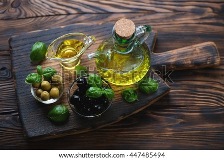 Rustic chopping board with extra virgin olive oil and olives